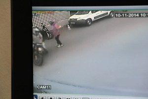 Assaltante em pé, perto da moto