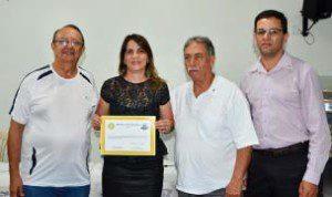 Rotarianos Carlinhos, Narcélio e Walter entregam diploma de participação a Leila