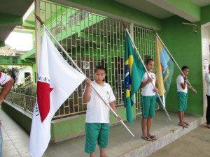 Alunos carregam as bandeiras de Minas, do Brasil e do Município