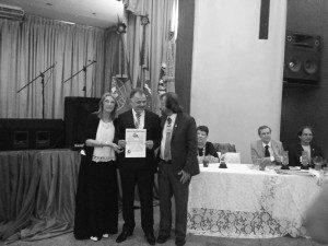 Eugênio recebendo o prêmio pelas mãos do escritor Luiz Poeta e da presidente da Editora Mágico de Oz