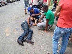 Jovem, que estava numa moto, sendo socorrido na Travessa Jorge Coura Filho