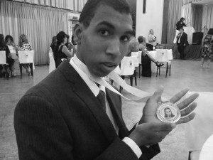 João Victor ostentando orgulhoso a medalha Monteiro Lobato recebida pelo pai