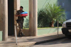 Policial saindo com documentos encontrados na casa de Angelita