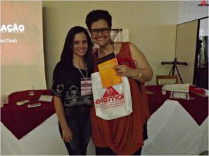 Alessandra Castro entrega seu livro para uma das ganhadora dos sorteios realizados durante o congresso